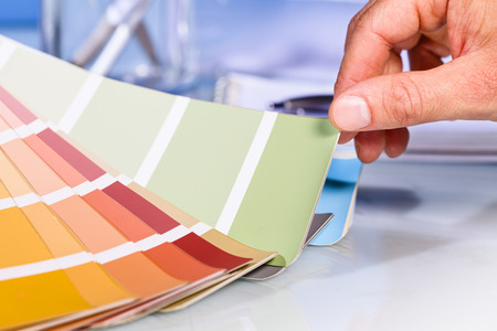 close up of artist hand browsing color samples in palette in studio background