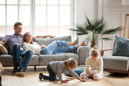98318581 - children sister and brother playing drawing together on floor while young parents relaxing at home on sofa, little boy girl having fun, friendship between siblings, family leisure time in living room